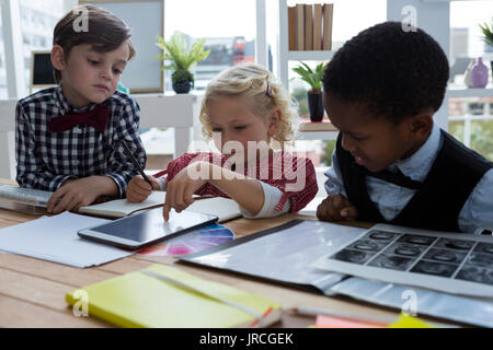 Businesswoman explaining to male colleagues over tablet in creative office - Stock Photo