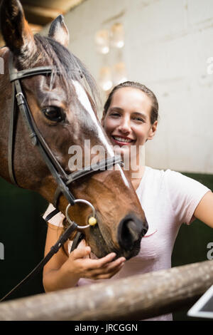 Portrait of female jockey by horse standing in stable - Stock Photo