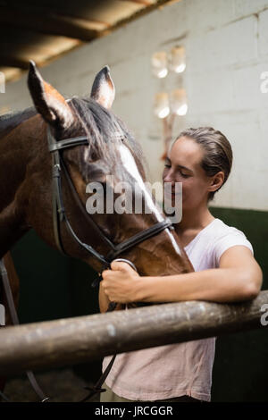 Smiling jockey standing by horse in stable - Stock Photo