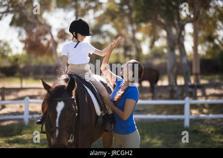 Side view of woman giving high five to girl sitting on horse in paddock - Stock Photo