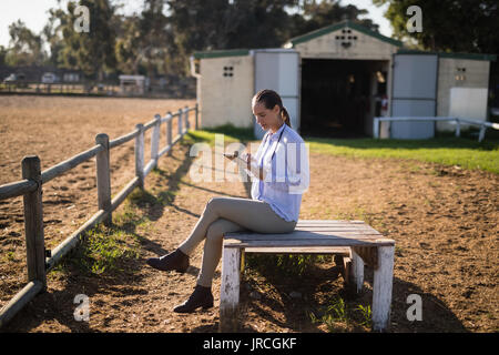 Female vet using digital tablet while sitting on seat at barn - Stock Photo