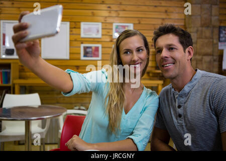 Young woman taking selfie with boyfriend through mobile phone in cafe - Stock Photo