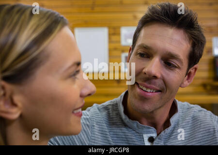 Close up of happy couple talking in cafe - Stock Photo