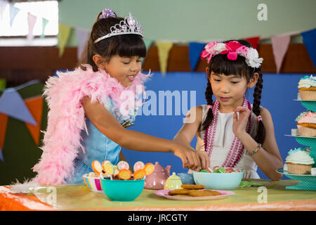 Cute girls having confectionery during birthday party at home - Stock Photo