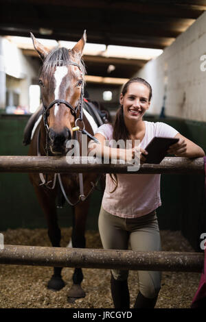 Portrait of smiling female jockey using digital tablet by standing by horse in stable - Stock Photo