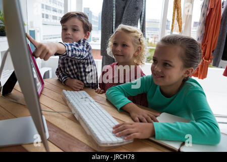 Businessman explaining to female colleagues over computer in creative office - Stock Photo