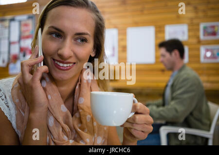 Close up of young woman talking on smart phone with man in background at cafe - Stock Photo
