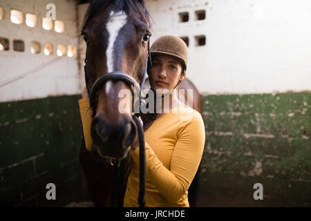 Portrait of female jockey standing by horse in stable - Stock Photo