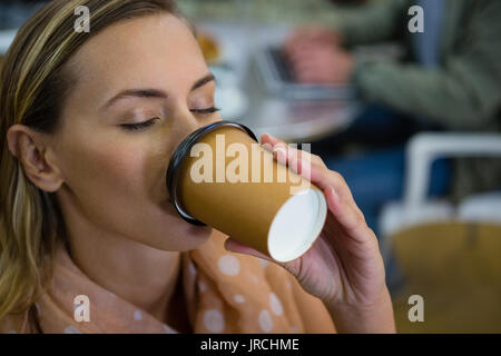 Close up of young woman with eyes closed having coffee at cafeteria