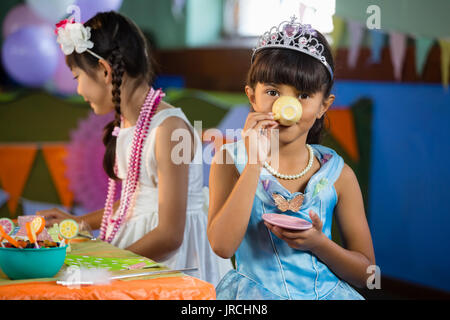 Cute girls having tea at table during birthday party at home - Stock Photo