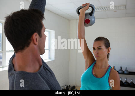 Confident athletes lifting kettlebells while facing each other in club - Stock Photo