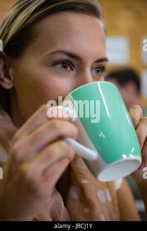 Close up of thoughtful young woman drinking coffee at cafe - Stock Photo
