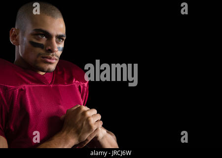 Close-up of determined American football player against a black background Stock Photo