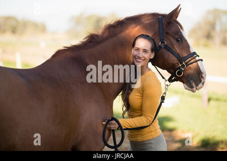 Portrait of female jockey standing by horse at barn - Stock Photo