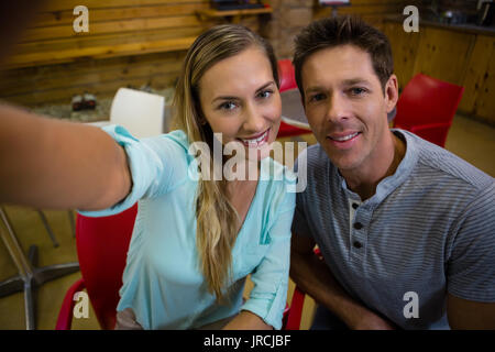 High angle portrait of happy couple sitting on chairs at cafe - Stock Photo