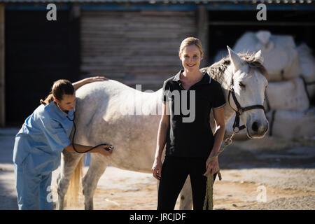 Portrait of female jockey standing by vet examining horse at barn - Stock Photo