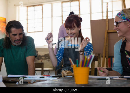 Happy adult students looking at painting while sitting in art class - Stock Photo