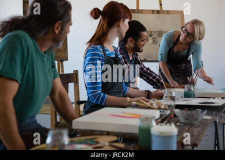 Smiling teacher examining painting while standing by student in art class - Stock Photo