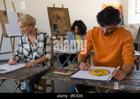 Adult students practicing painting on book at table in art class - Stock Photo