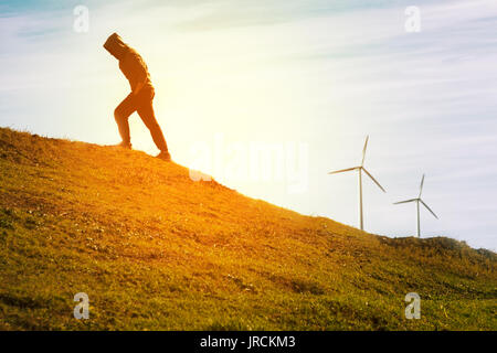Man climbig a hill in a sunny day behind him two wind turbines - Stock Photo