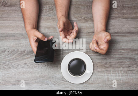 top angle view of three man's arms holding phone and drinking coffee - Stock Photo