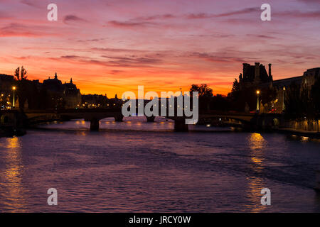Spectacular crimson sunset over the Seine River in Paris - Stock Photo