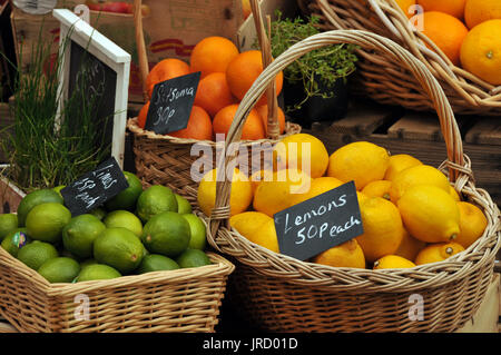 oranges and lemons fruit for sale in baskets at a market fruit and vegetables - Stock Photo