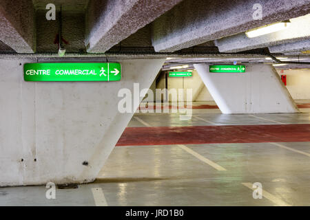 Luminous signs indicating the direction to the commercial center in an old decrepit underground parking lot. - Stock Photo