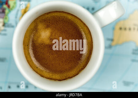 Cup of freshly brewed espresso coffee viewed close up from above on a world map background - Stock Photo
