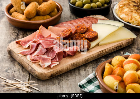 Traditional spanish tapas. Croquettes, olives, omelette, ham and patatas bravas on wooden table - Stock Photo