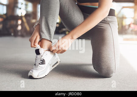 Young female exercise in the gym tie shoelaces - Stock Photo