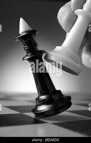 Conceptual image depicting making a strategic move with a hand moving a chess piece on a chessboard during a game of skill