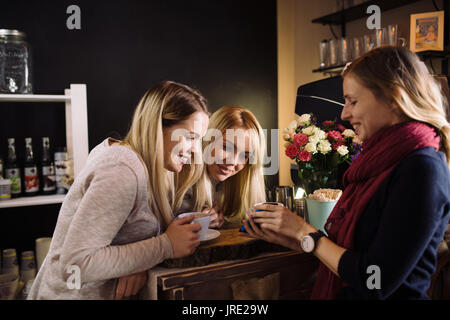 One young woman showing something on smartphone to two blonde sisters twins in cafe. Three women friends looking - Stock Photo