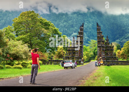 Young man traveler backpacker enjoy amazing morning view traditional hindu gate at summer day on background mountain - Stock Photo