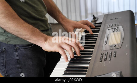Man playing electric piano or electronic keyboard - Stock Photo