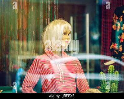 Woman mannequin inside the shop, view through the window with reflections - Stock Photo