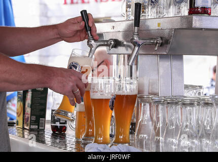 Berlin, Germany. 4th Aug, 2017. A staff member prepares beer for customers during the 21st International Berlin - Stock Photo