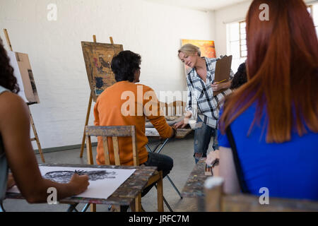 Female teacher examining students painting at table in art class - Stock Photo