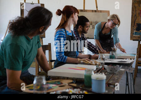 Teacher examining painting while standing by student in art class - Stock Photo
