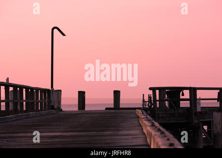 Pink sunset hues over wooden jetty wharf on Fraser Island Queensland Australia - Stock Photo