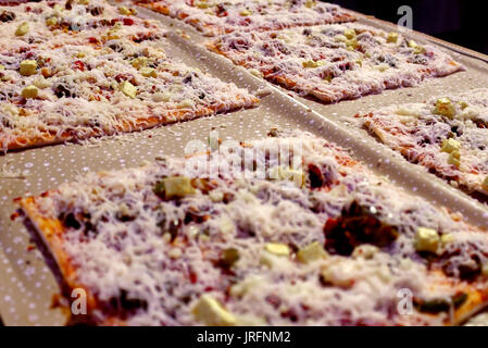 many square pan pizza with cheese are ready to serve on family gathering - Stock Photo