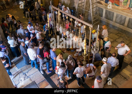 A crowd of penitents gathers around the Stone of Annointing in the Church of the Holy Sepulchre in the Old City - Stock Photo