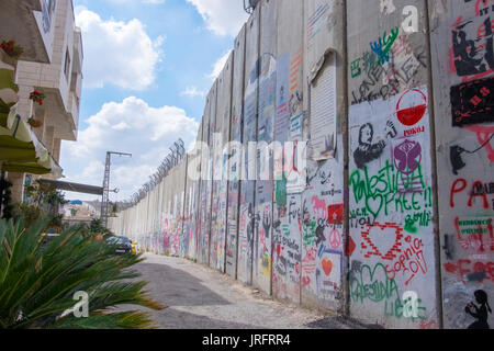 The grafitti filled wall separating Palestine from Israel as it divides the city of Bethlehem in the Occupied Territories - Stock Photo