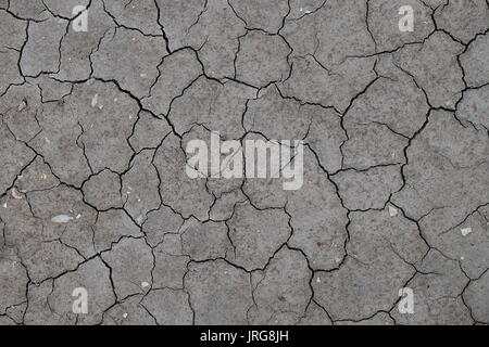 Cracked soil from a dried river bed. Weather and climate change - Stock Photo