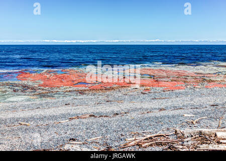 Red colorful rocks on beach shore of Saint Lawrence river in Sainte-Luce, Quebec, Canada in Gaspe region - Stock Photo