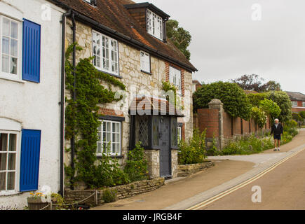 A lone elderly male walks down a street of picturesque terraced houses toward the marina in the village of Warsash - Stock Photo