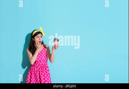 pretty attractive woman wearing cute dress standing on blue background and looking at donut food feeling fear about - Stock Photo