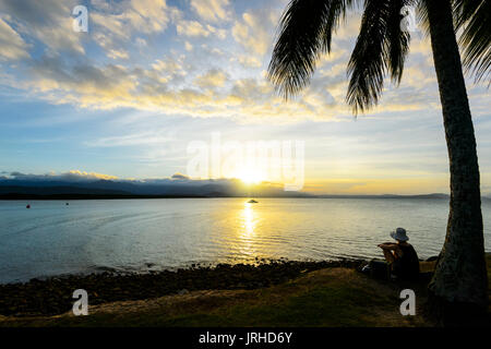 Female watching the sunset from Rex Smeal Park, Port Douglas, Far North Queensland, FNQ, QLD, Australia - Stock Photo