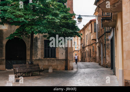 Pollensa, Mallorca, Spain - May 24, 2015: Woman walks along the narrow winding streets in historical town part of - Stock Photo
