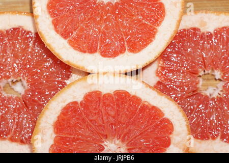 Grapefruit cut on slices and arranged on wooden plate shining from reflected light - Stock Photo